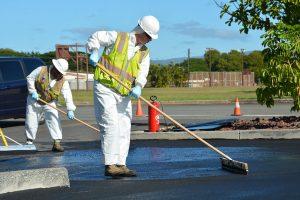 man applying seal coat to asphalt