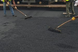 Two Workers spreading asphalt