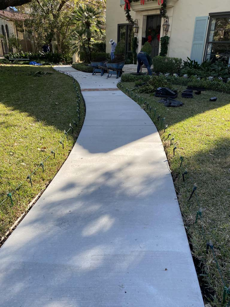 Image of residential concrete sidewalk connecting to concrete driveway