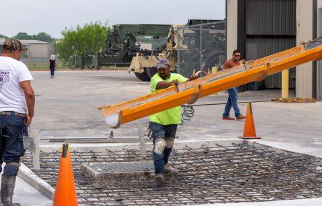Image of crew pouring concrete into tied rebar around storm drain