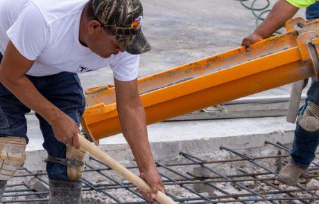 Image of concrete crew member spreading concrete ready mix