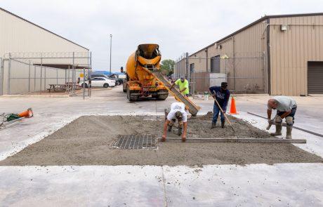 Image of concrete crew spreading and finishing concrete around storm drain