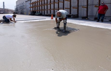 Image of a concrete finisher smoothing out poured concrete around a storm drain