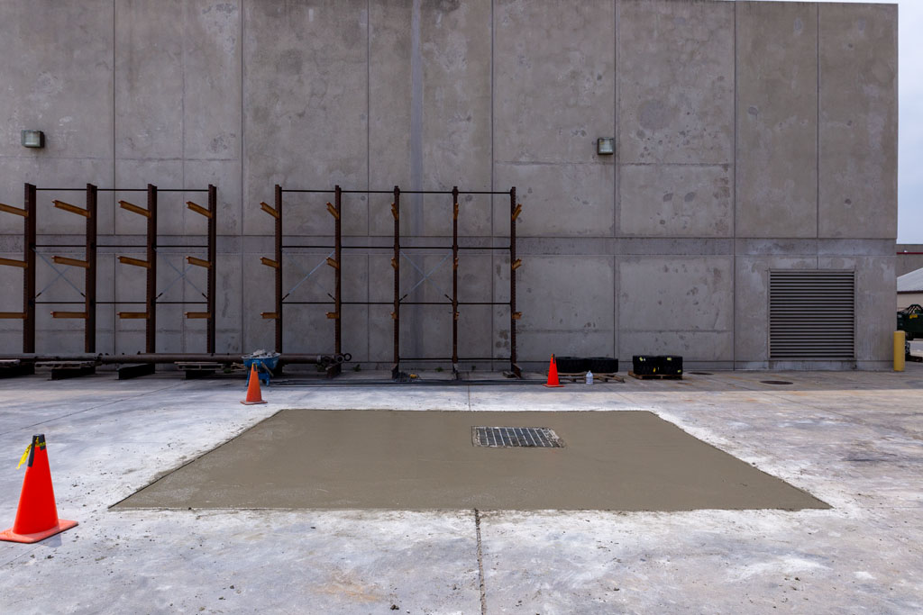 Image of poured concrete that is finished and curing around a storm drain